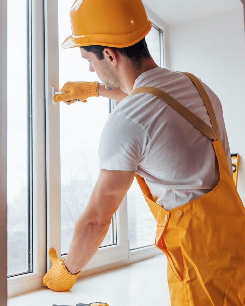 Handyman in yellow uniform installs new window. House renovation conception